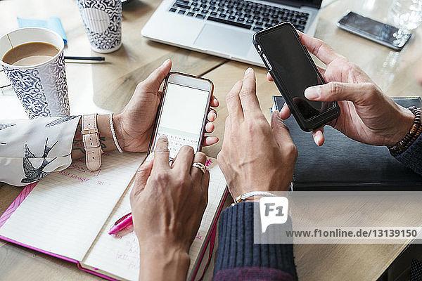 Ausgeschnittenes Bild von Geschäftsleuten  die im Büro Mobiltelefone benutzen