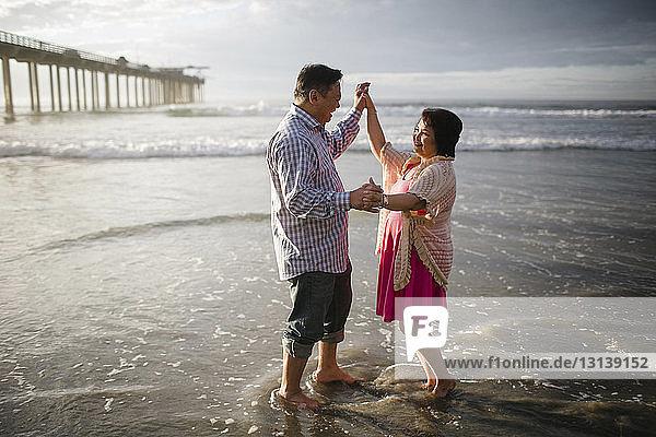 Seitenansicht eines Paares  das am Strand am Ufer tanzt
