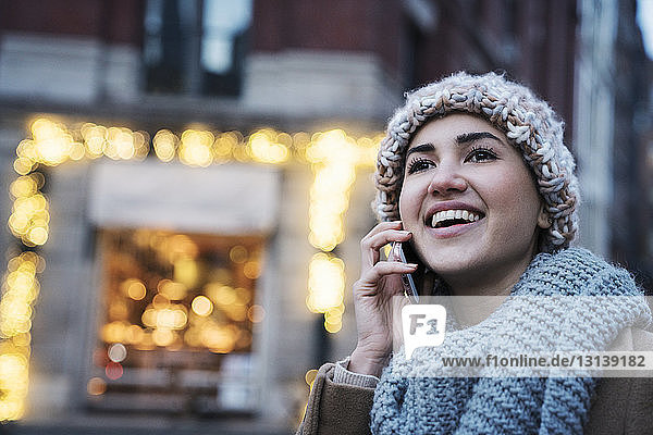 Close-up of happy woman talking on mobile phone in city