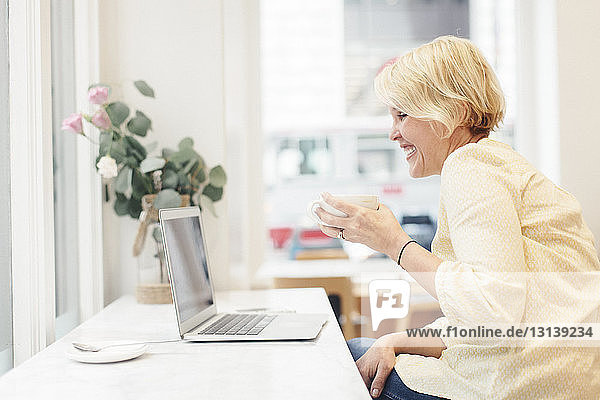 Cheerful woman holding coffee cup while looking at laptop computer in cafe