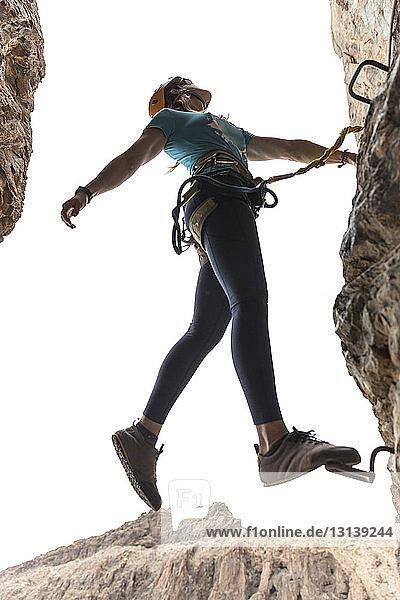 Niedrigwinkelansicht einer Wanderin,  die auf einer Sprosse steht,  die in einer Felsformation montiert ist