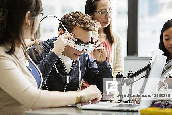 Männlicher Student trägt eine Virtual-Reality-Brille  während er im Klassenzimmer bei Freunden sitzt