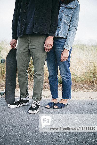 Niedriger Anteil von Freunden mit Skateboard auf der Straße stehend