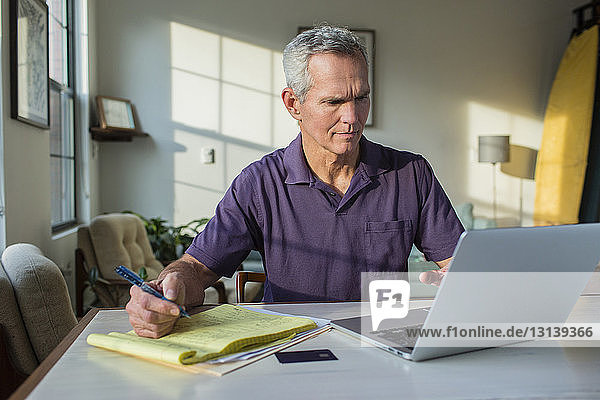 Mature man writing on note pad while using laptop computer at home