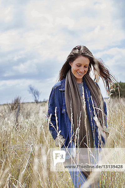 Woman smiling while walking on field against sky