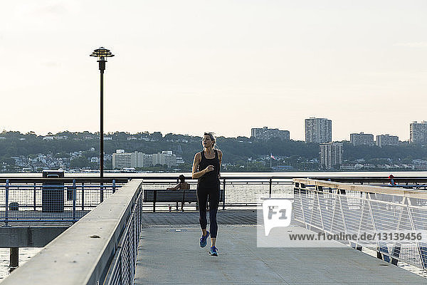 Woman jogging while exercising on bridge against clear sky in city