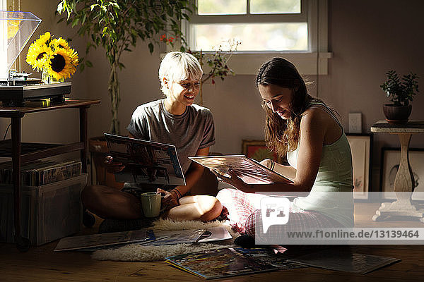 Happy female friends looking at vinyl records while sitting on floor at home