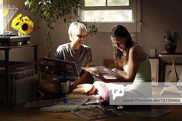 Glückliche Freundinnen  die sich zu Hause auf dem Boden sitzend Vinyl-Schallplatten anschauen