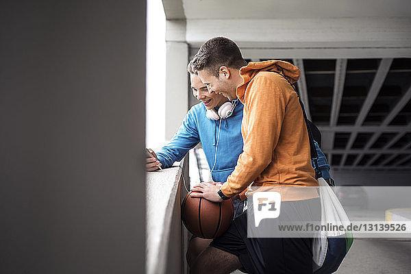 Fröhliche männliche Freunde mit Basketball mit Smartphone auf dem Parkplatz
