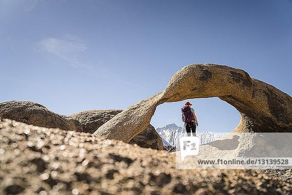 Rückansicht einer Frau mit Rucksack  die an einem sonnigen Tag an einer Felsformation steht