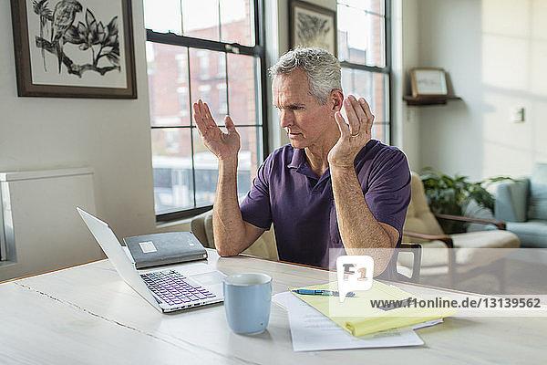 Schockierter reifer Mann gestikuliert  während er auf Laptop-Computer auf dem Tisch im Wohnzimmer blickt