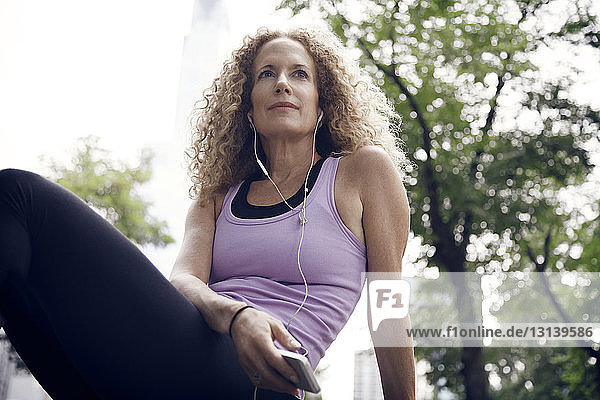 Low angle view of athlete listening to music while sitting at park