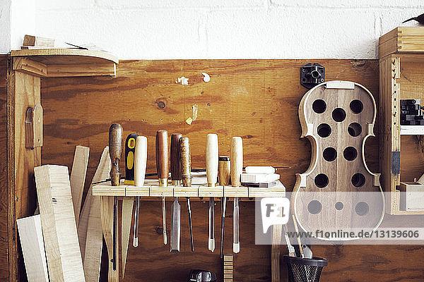 Handwerkzeuge und unvollständige Geigenaufhängung in der Werkstatt Handwerkzeuge und unvollständige Geigenaufhängung in der Werkstatt