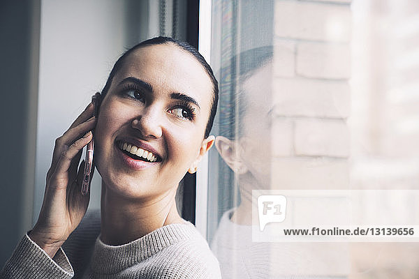 Happy woman looking through window while talking on mobile phone at home