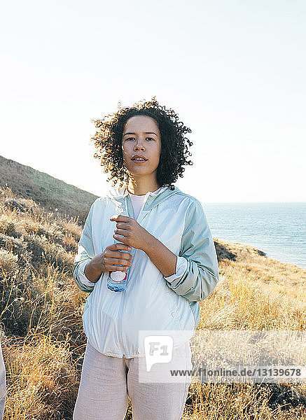Portrait of woman holding bottle while standing on hill by sea against clear sky