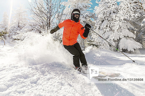 Full length of young man skiing on snow against trees during winter