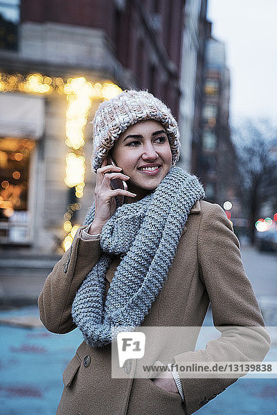 Smiling woman talking on mobile phone in city at dusk