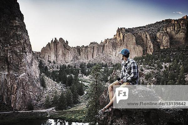 Mann sitzt auf Fels gegen Berge