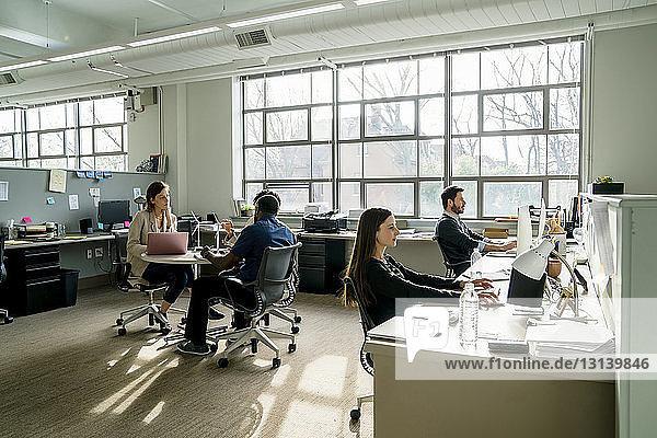 Geschäftsleute diskutieren  während sie im Büro am Schreibtisch sitzen