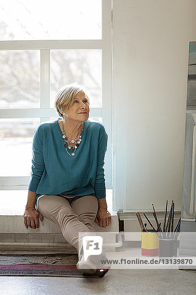 Woman looking up while sitting on window sill