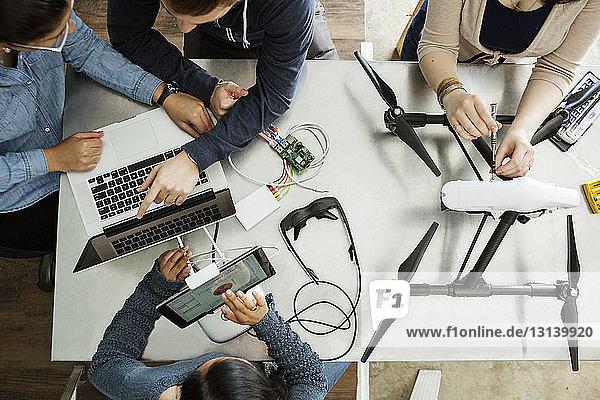 Draufsicht auf Freunde  die bei Tisch an elektrischen Geräten arbeiten