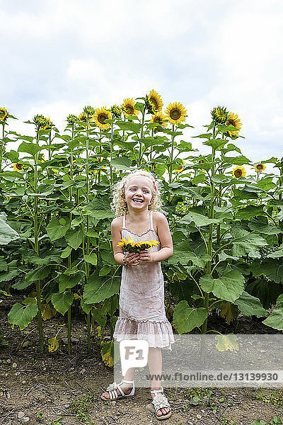 Cheerful girl holding sunflowers while standing against plants