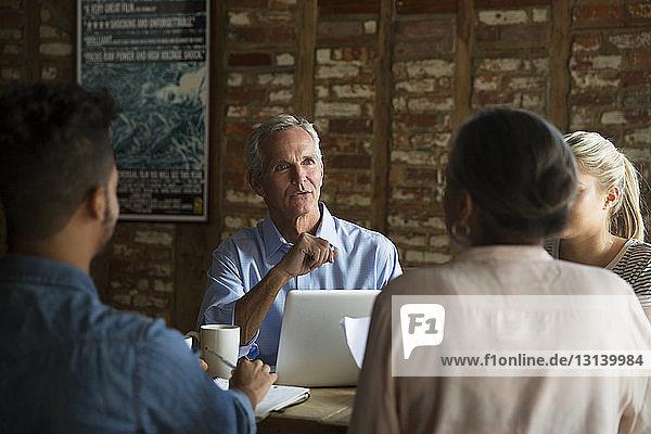Zuversichtlicher Geschäftsmann im Gespräch mit Kollegen während eines Treffens im Café