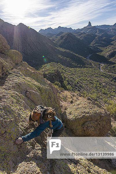 Hochwinkelaufnahme eines Mannes  der einen Deutschen Schäferhund im Rucksack trägt  während er einen Berg gegen den Himmel besteigt