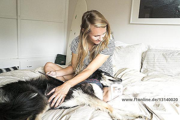 Glückliche Frau spielt zu Hause mit Hund