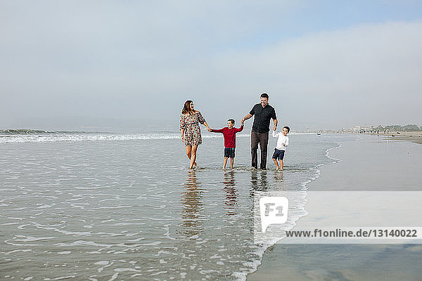Family holding hands while walking on shore at beach against sky