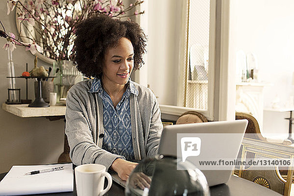 Smiling woman using laptop computer while sitting at table