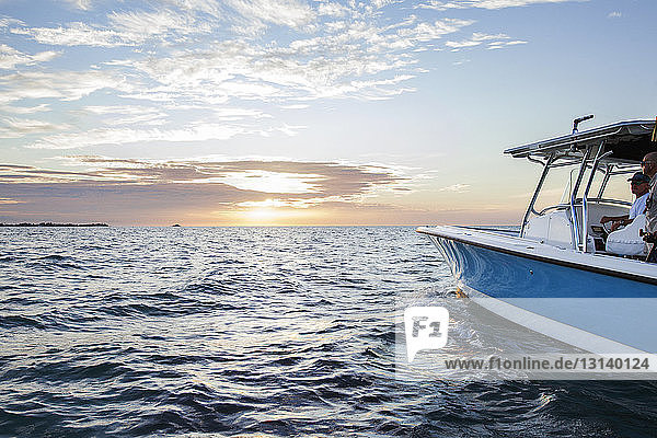 Men travelling on boat at sea against sky during sunset
