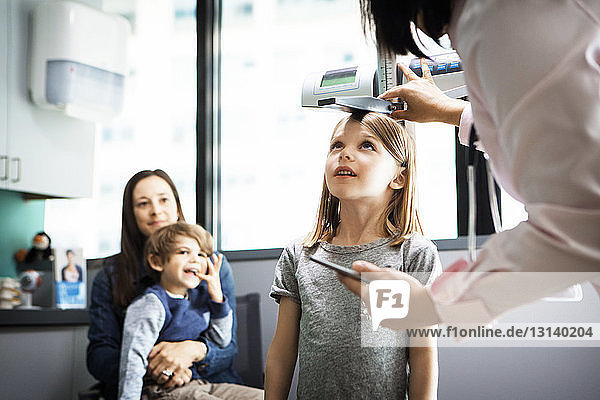 Doctor measuring girl's height while family sitting at clinic