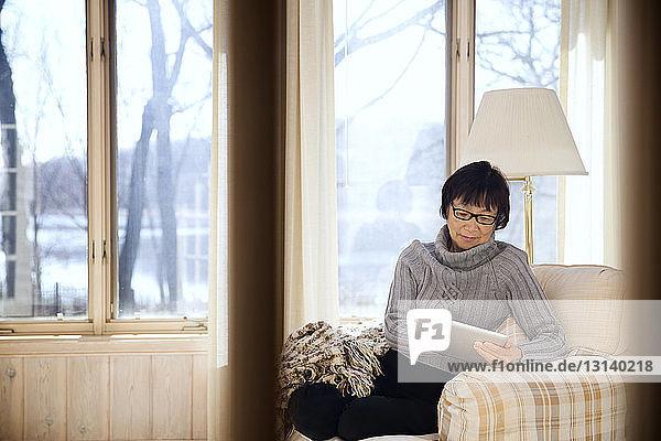 Ältere Frau benutzt Tablet-Computer  während sie zu Hause auf einem Sessel sitzt