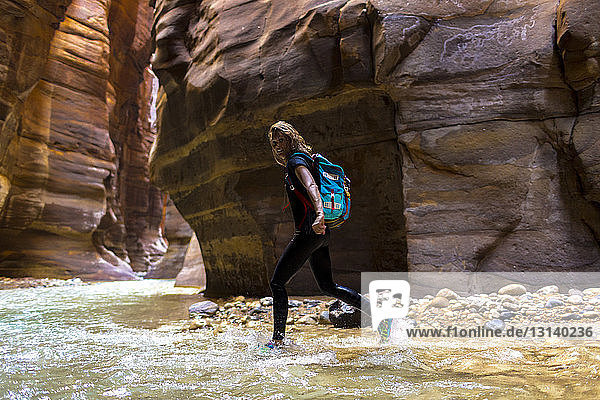 Portrait of female backpacker walking in river by mountains