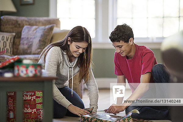 Siblings wrapping Christmas gift at home