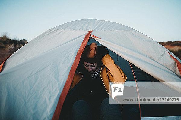 Wanderin mit Hut  die im Zelt sitzt
