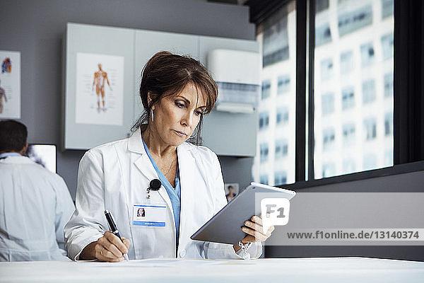 Ärztin benutzt Tablet-Computer beim Schreiben am Schreibtisch in der Klinik