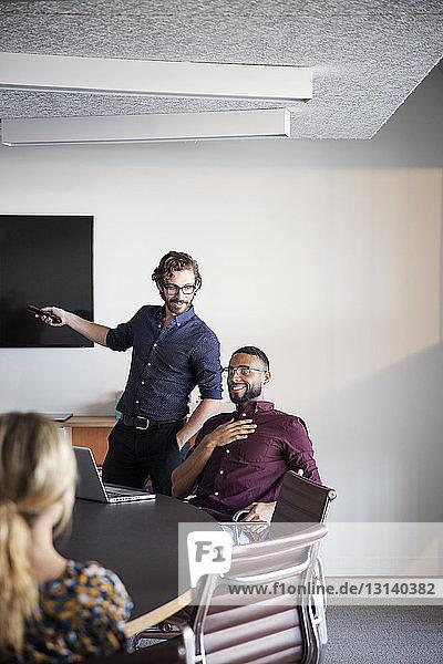 Geschäftsmann erklärt den Kollegen bei Besprechung im Sitzungssaal
