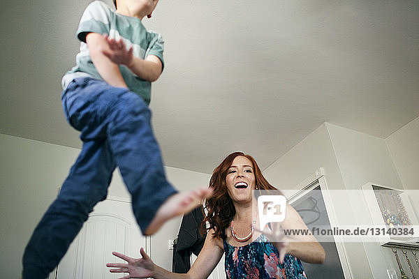 Low angle view of boy jumping with mother at home