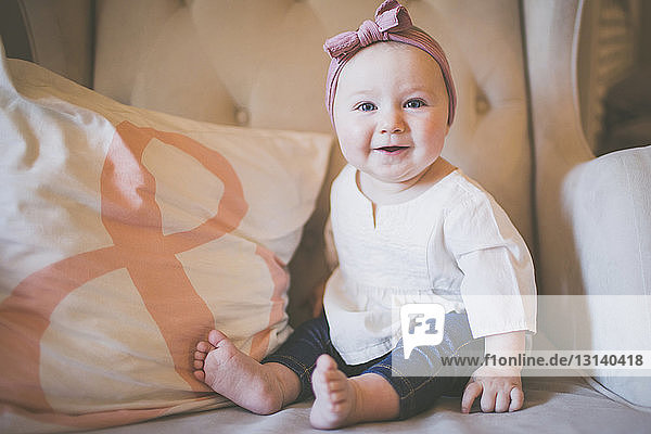Portrait of smiling baby girl sitting on armchair at home