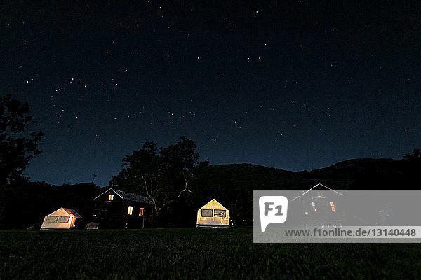 Beleuchtete Zelte und Häuser auf dem Feld gegen den nächtlichen Sternenhimmel