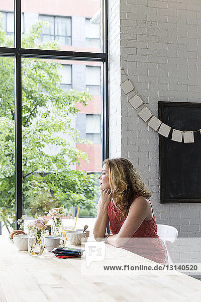 Thoughtful woman with hand on chin looking through window while sitting in cafe