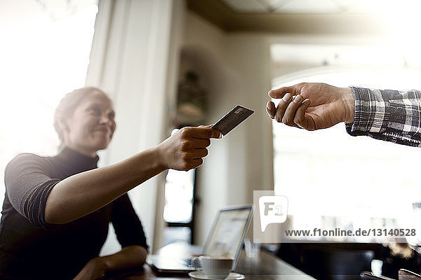 Smiling woman giving credit card to waiter in cafe