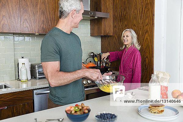 Mann mischt Eier  während er die Frau bei der Zubereitung des Essens in der Küche beobachtet