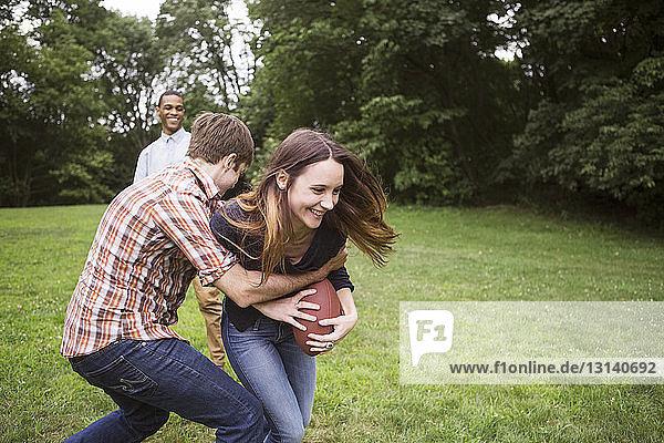 Mann zieht Frau zurück  die den Fussball hält  während ein Freund auf dem Rasen steht