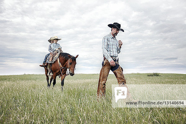 Father walking while sons riding horse on field against cloudy sky