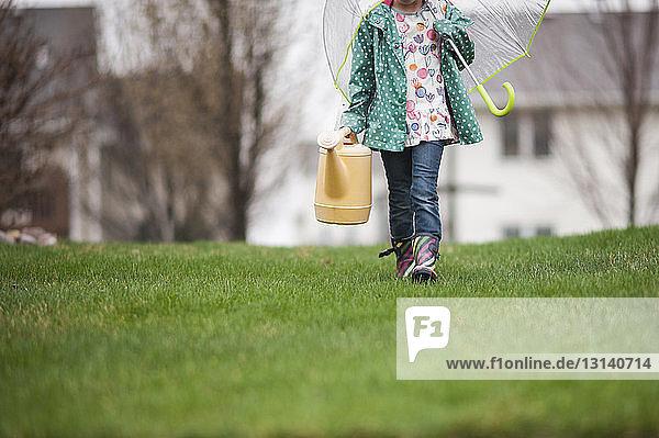 Mädchen mit Gießkanne und Regenschirm im unteren Teil des Mädchens beim Gehen auf Grasfeld