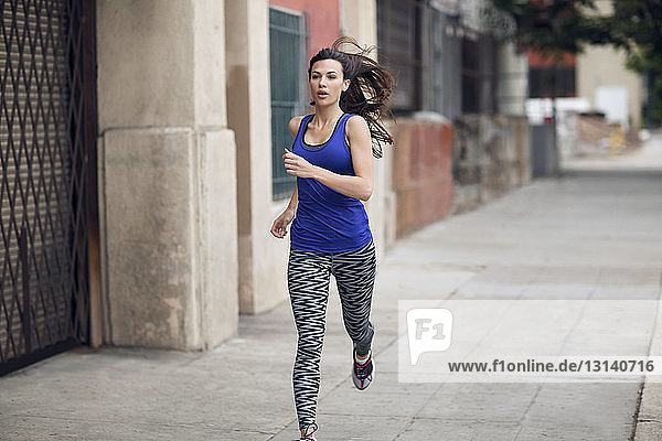 Determined sportswoman running on sidewalk
