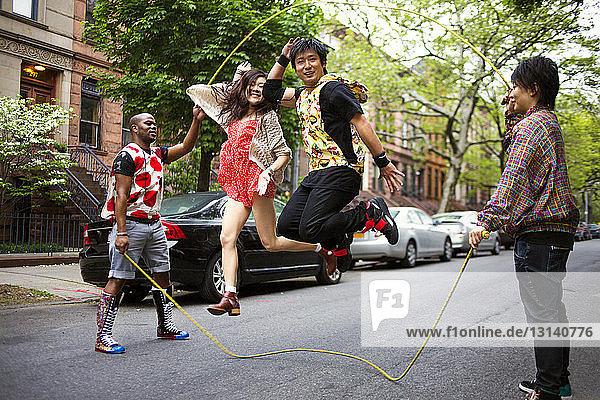 Freunde genießen Doppel-Holländisch auf der Straße gegen parkende Autos
